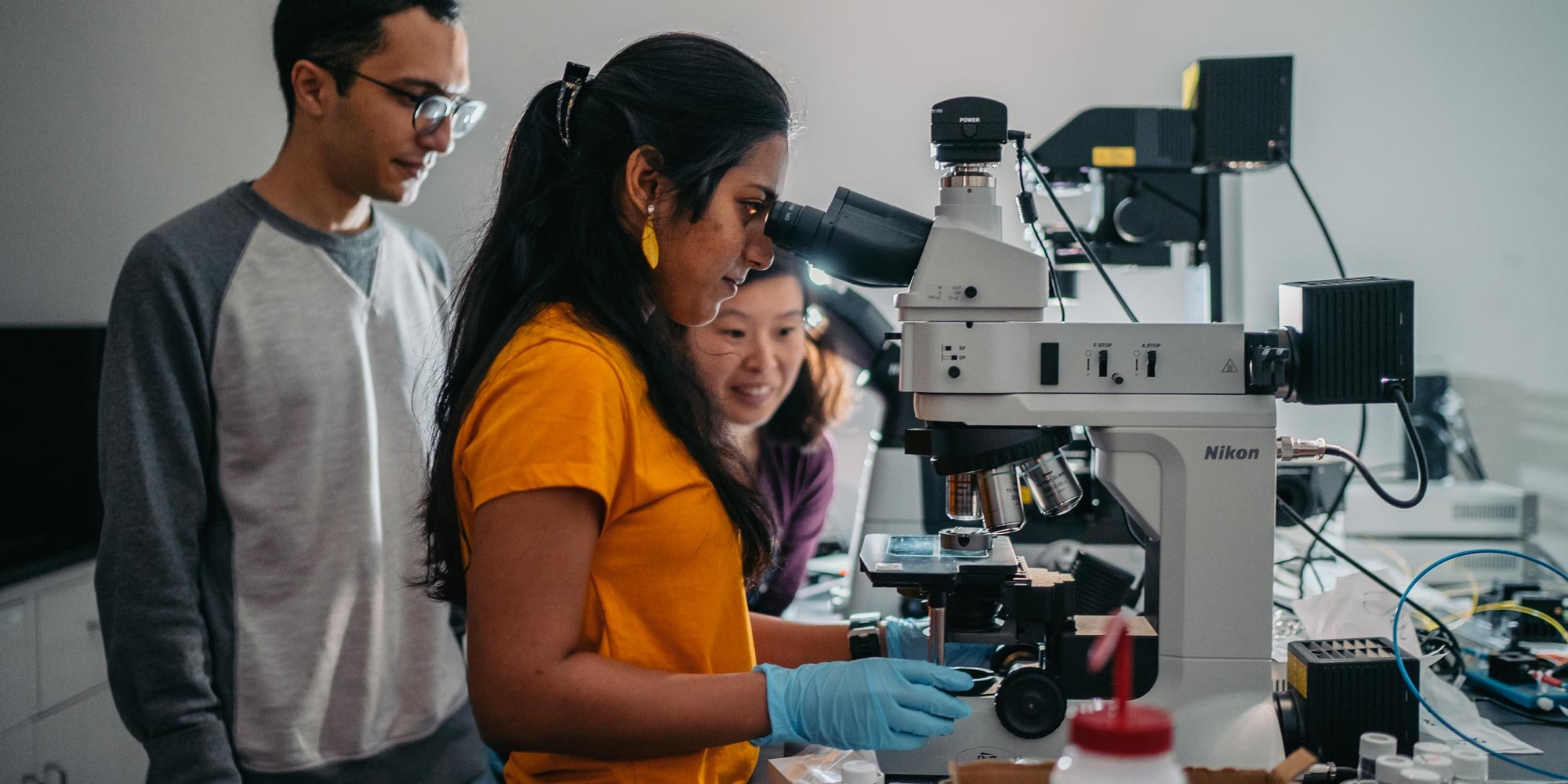 a female student looking in a microscope with two students beside her